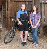 Officer in uniform with bicycle standing beside woman in jeans
