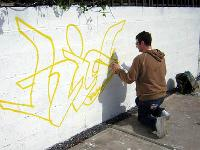 Image of a young man painting yellow graffiti