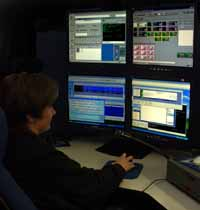 Image of a woman sitting at a dispatch center with four computer screens