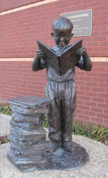 Statute of a child reading a book