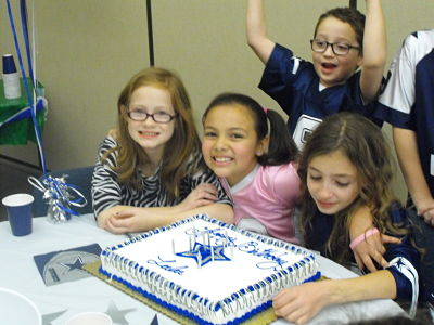 Four children around a cowboys birthday cake