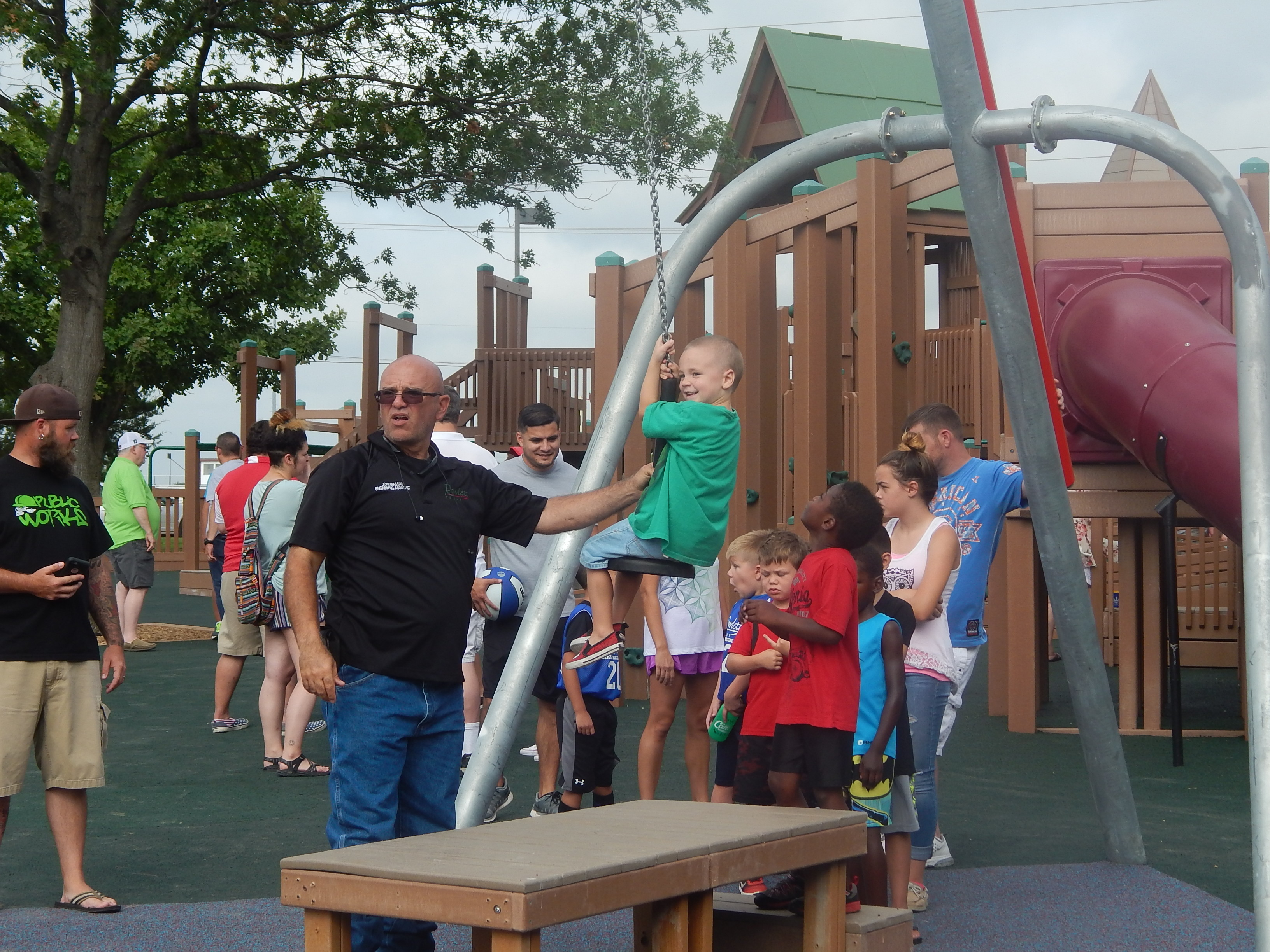 Adult hold child on swing zip line in playground