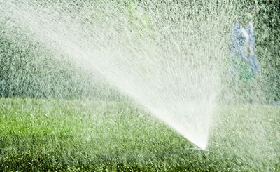 Green lawn with irrigation sprinkler running