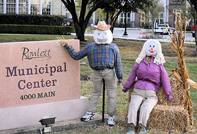 Two scarecrows next to the City Hall sign