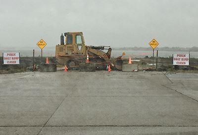 Bulldozer with signs next to it reading public boat ramp closed