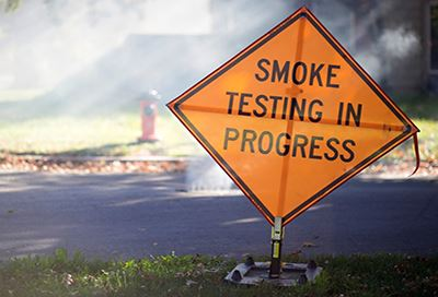 Caution sign with the text: SmokeTesting In Progress
